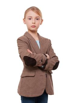 Уверенный в себе маленький лидер. уверенная маленькая девочка в строгой одежде, скрестив руки, стоя изолированной на белом