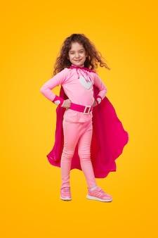 Confident little superhero holding hands on waist