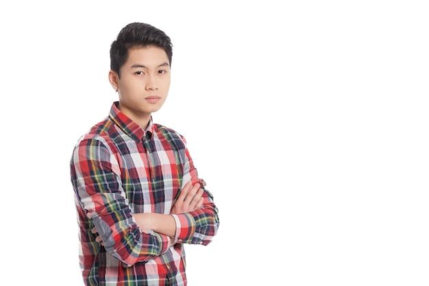 自信を持って見てください。腕を組んで笑顔の中国の10代の少年の笑顔と白で孤立して立っている間笑顔