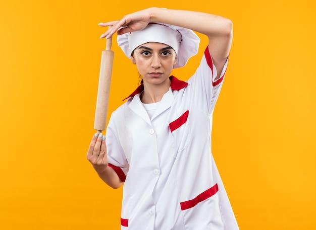Уверенно глядя в камеру молодая красивая девушка в униформе шеф-повара держит скалку