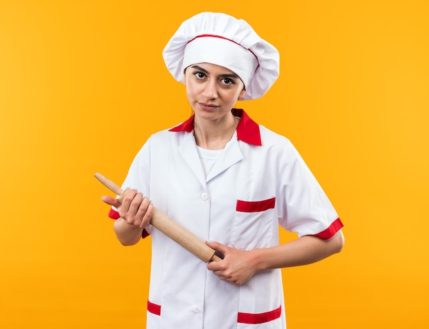 麺棒を保持しているシェフの制服を着た若い美しい少女のカメラを見て自信を持って