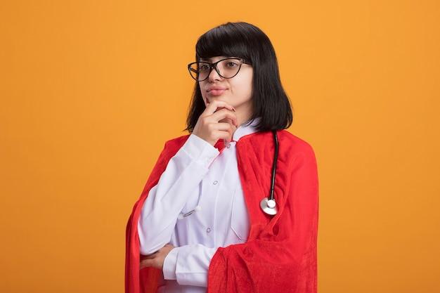 의료 가운과 안경 망토와 청진기를 입고 측면 젊은 슈퍼 히어로 소녀를보고 자신감은 턱을 잡고