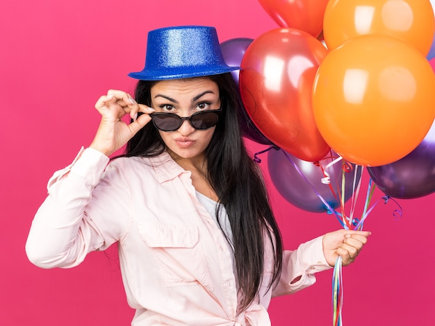 Confident looking camera young beautiful girl wearing party hat and glasses holding balloons