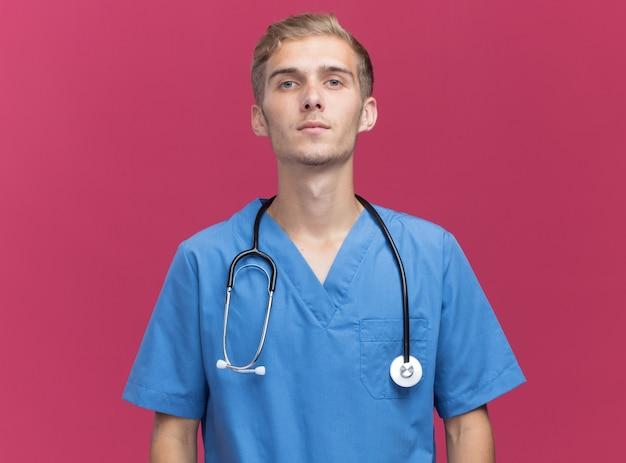 Fiducioso che guarda l'obbiettivo giovane medico maschio che indossa l'uniforme del medico con lo stetoscopio isolato sulla parete rosa con lo spazio della copia