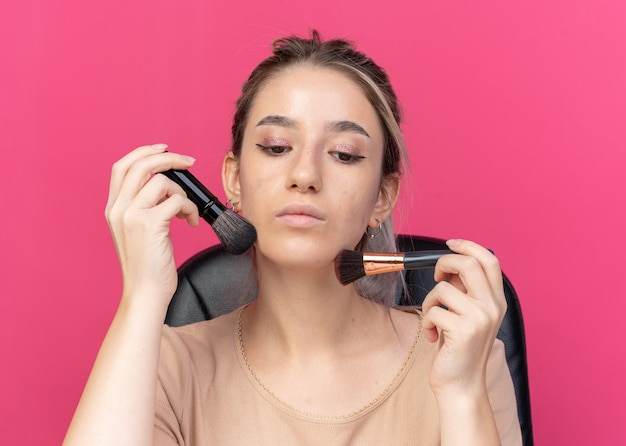 Confident looking down young beautiful girl applying powder blush isolated on pink wall