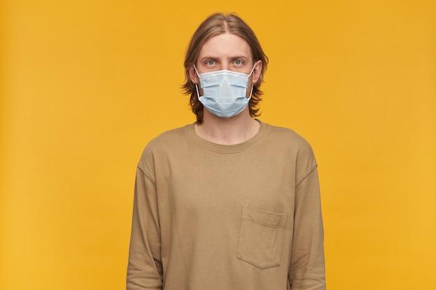Уверенно выглядящий мужчина, красивый бородатый парень со светлой прической. в бежевом свитере и медицинской защитной маске. изолированные над желтой стеной