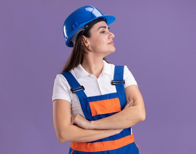 Fiducioso guardando a lato le giovani donne del costruttore in uniforme che si incrociano le mani isolate sul muro viola