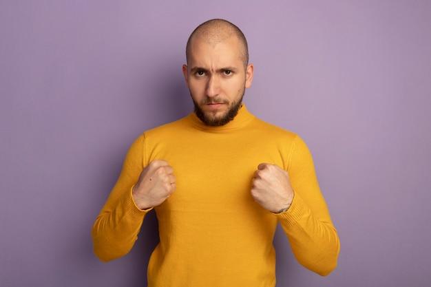 보라색에 고립 된 포즈 싸움에 서있는 자신감을 찾고 똑바로 젊은 잘 생긴 남자