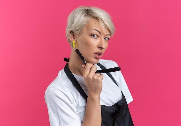 ピンクの壁に分離されたストレートかみそりを保持している制服を着た自信を持って若い美しい女性の理髪店