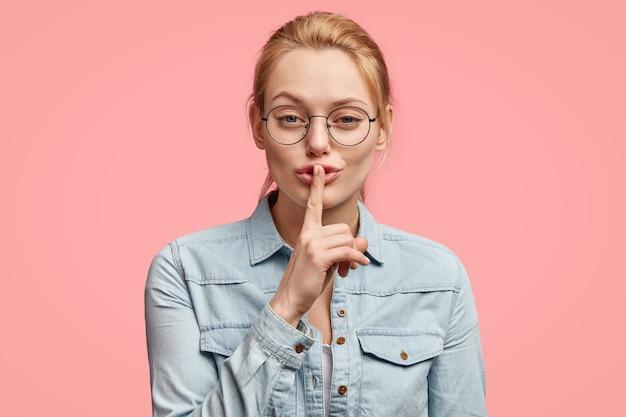 自信を持って素敵な若いブロンドの女性は、静けさの兆候を示し、誰かに秘密を伝え、唇の前指に触れます