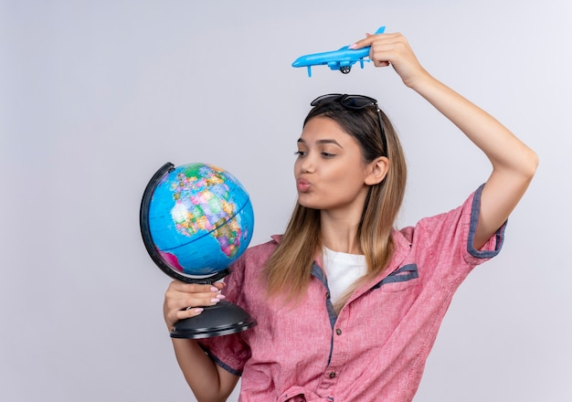 A confident lovely young woman wearing red shirt in sunglasses looking at a globe while flying a blue toy plane on a white wall