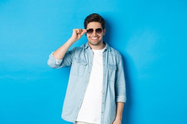 L'uomo macho fiducioso indossa gli occhiali da sole, sembra fresco e sfacciato, in piedi su sfondo blu