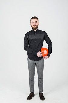 Confident male architect holding an orange hardhat against white background