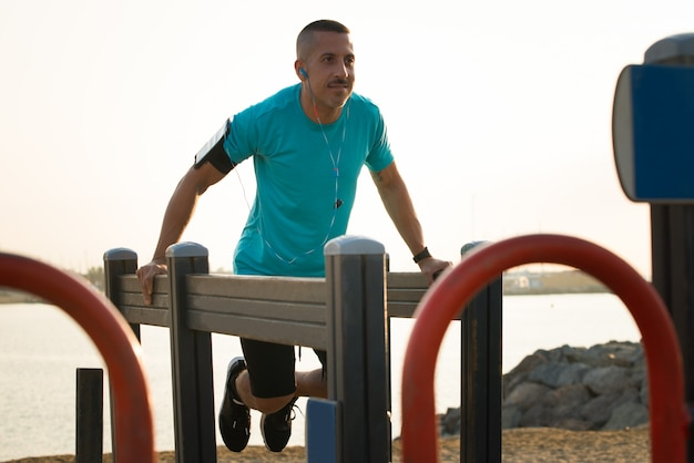Confident male athlete exercising on parallel bars