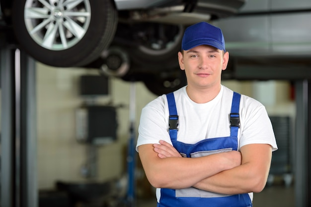 Confident male auto mechanic in workshop.