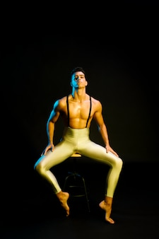 Confident male ballet dancer sitting in spotlight