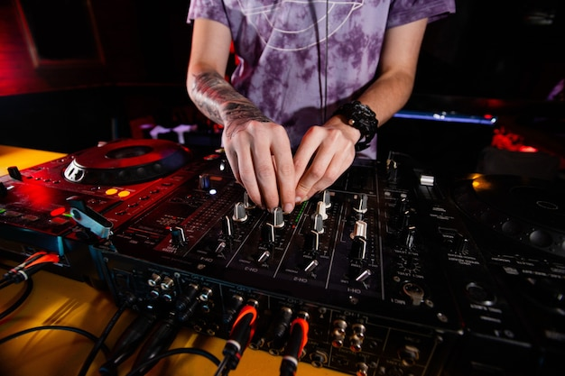 턴테이블에서 자신감 남성 디스크 자키. dj는 파티 중에 나이트 클럽에서 가장 유명한 cd 플레이어로 연주합니다. edm, 파티 개념. 나이트 클럽 생활. 총을 닫습니다.