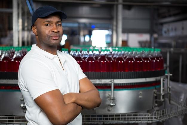 Impiegato maschio sicuro con le braccia incrociate in piedi in fabbrica