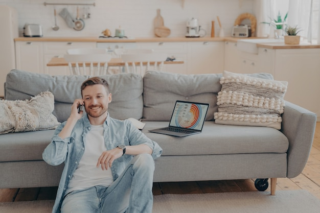 Confident male freelance worker calling his employer to tell him good news about project, making another client satisfied, laptop with infographics, sitting on floor while resting against couch