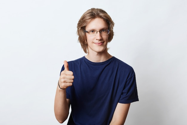 Confident male freelancer with stylish hairdo, wearing spectacles, showing ok sign while raising his thumb, agreeing with something. young manager posing on white. career concept