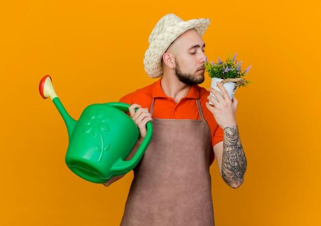원예 모자를 쓰고 자신감있는 남성 정원사는 물을 수 있고 화분에 꽃 냄새를 맡습니다.