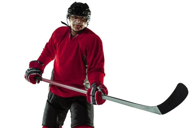 自信がある。アイス コートと白い背景にスティックを持つ男性のホッケー選手。スポーツマン着用の機器とヘルメットの練習。スポーツのコンセプト、健康的なライフスタイル、動き、動き、行動。
