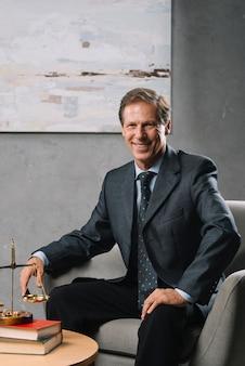 Уверенный мужской зрелый адвокат, сидящий в офисе