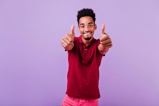 陽気な笑顔でポーズをとる自信のある男性モデル。楽しんでいるアフリカのハンサムな男。