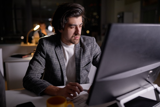 밤에 컴퓨터 작업을 하는 자신감 있는 남성 프로그래머. 테이블 조명이 켜졌습니다. 공식적인 마모에 백인 남자는 어두운 사무실에서 사무실에서 일에 종사. 네트워킹, 프리랜서, 마감. 복사 공간