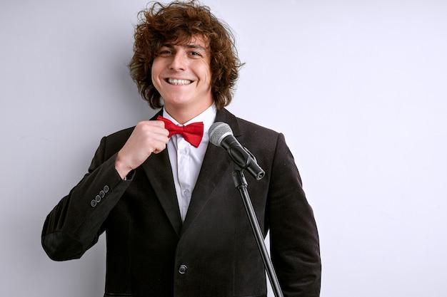 Уверенный мужской спикер стоит, фиксируя галстук перед выступлением с микрофоном, не боится публичных выступлений, улыбается