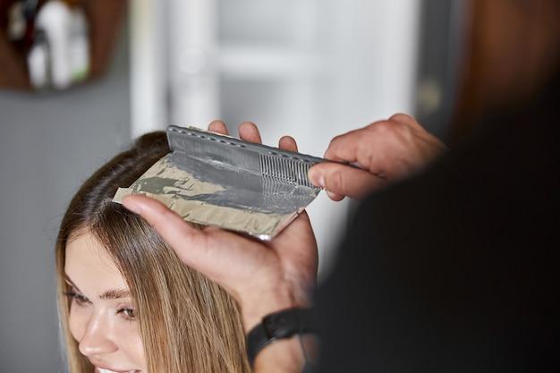 自信のある男性スタイリストが金髪の白人女性クライアントの髪を染めています