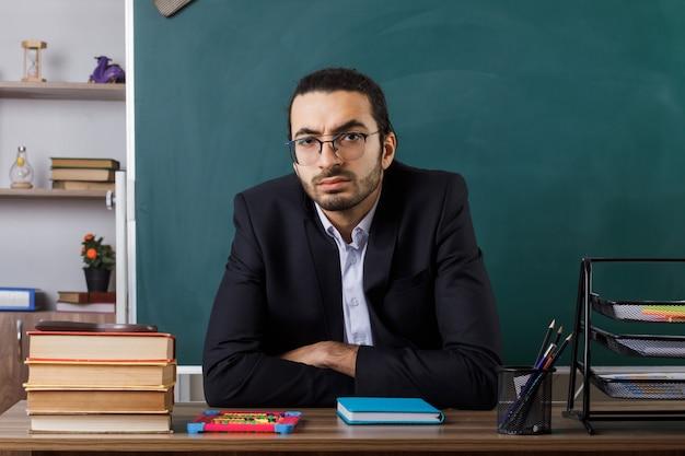 Fiducioso insegnante maschio con gli occhiali seduto al tavolo con gli strumenti della scuola in classe