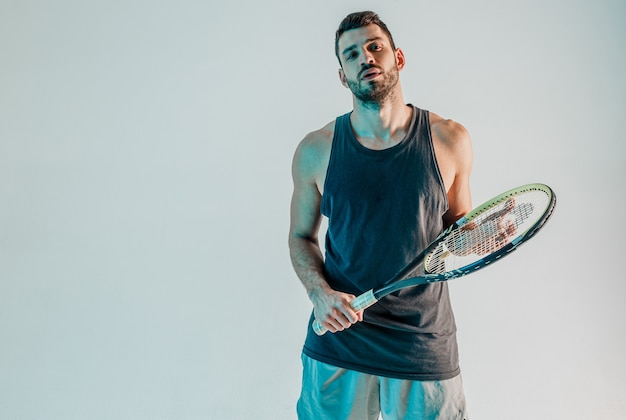 Confident male tennis player with racquet. portrait of young bearded european sportsman looking at camera. isolated on turquoise background. studio shoot. copy space