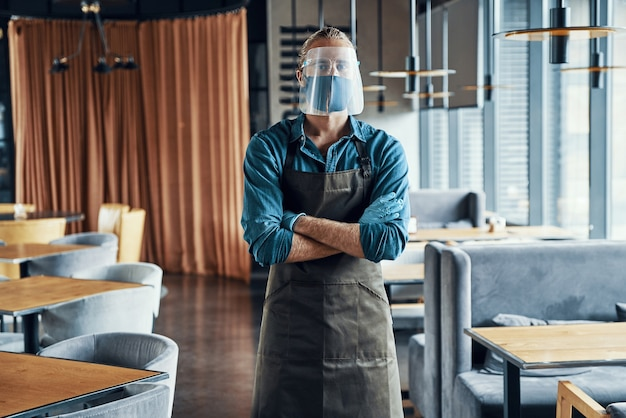 Уверенный мужчина-официант в защитном щитке со скрещенными руками
