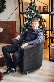 Confident male wearing shirt sitting on a comfortable armchair on of christmas tree.