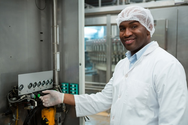 Уверенный мужчина работает на машине на фабрике соков