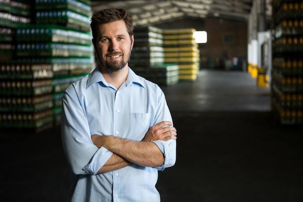 倉庫に立っている自信のある男性労働者