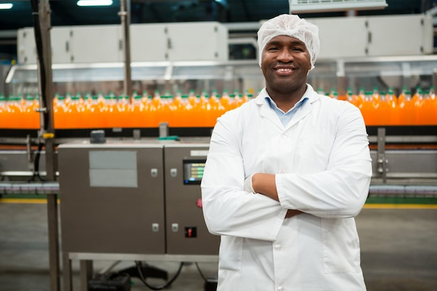 Confident male worker standing in juice factory