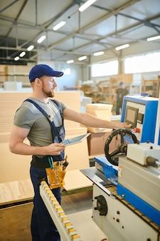 Уверенно мужского пола работника, используя компьютер фабричной машины