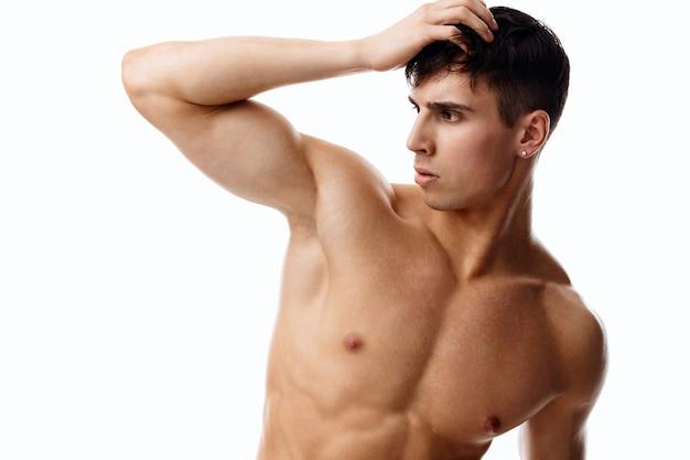 Уверенный в себе мужчина-спортсмен с накачанным торсом касается его головы рукой на светлом фоне