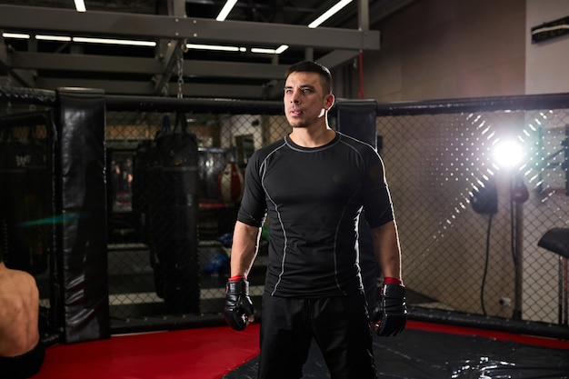 Confident man boxer in gloves standing after fight. young boxer during workout. concept of strentgh and motivation. portrait of male looking ai side seriously