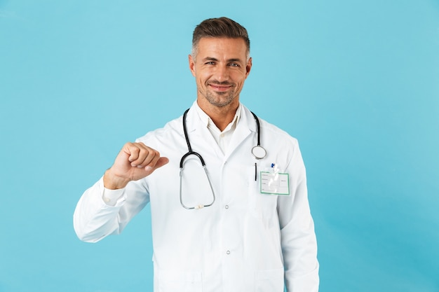 Confident man doctor wearing uniform standing isolated over blue wall, pointing at himself