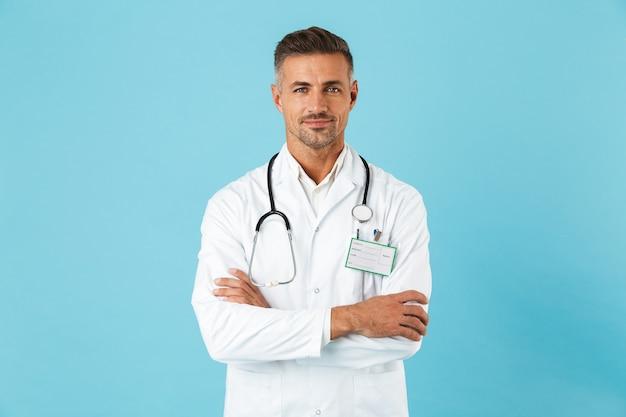 파란색 벽 위에 절연 유니폼 서 입고 자신감 남자 의사, 팔 접혀