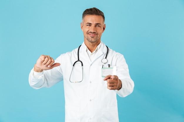Уверенный мужчина-врач в униформе, стоящий изолированно над синей стеной, указывая на себя