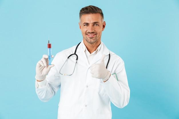 Уверенный мужчина-врач в униформе стоит изолированно над синей стеной, показывая шприц с красной жидкостью