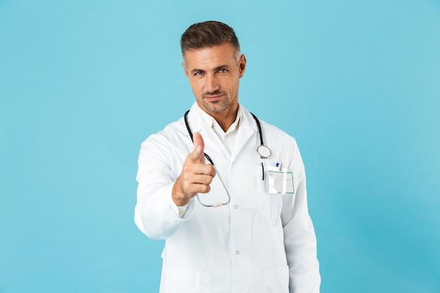 파란색 벽 위에 절연 유니폼 서 입고 자신감 남자 의사
