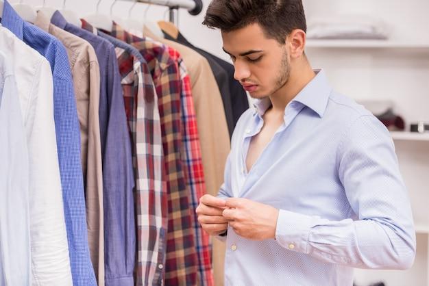 Confident man dressing blue shirt in dressing room.