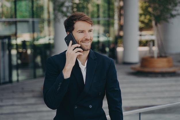 Уверенный в себе мужчина-предприниматель, одетый в формальную одежду, делает телефонный звонок в роуминге