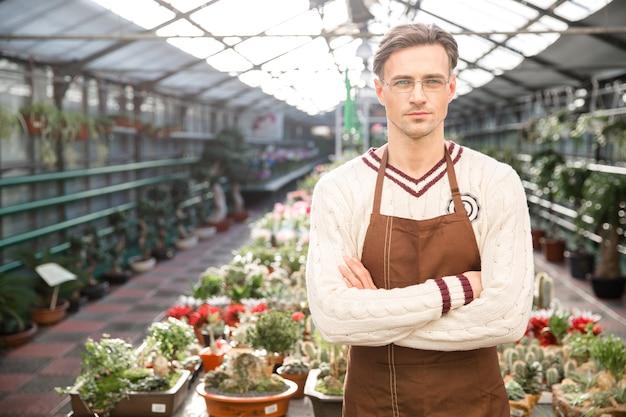 갈색 앞치마에 자신감이 남자 정원사와 팔을 넘어 온실에 서있는 안경