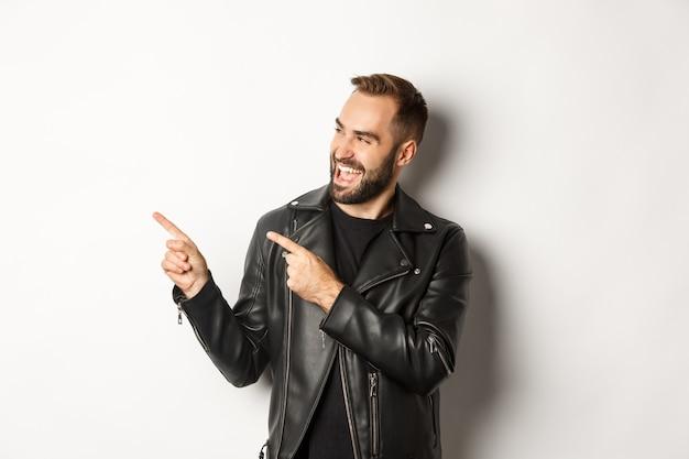 검은 가죽 재킷을 입은 자신감 넘치는 남자, 프로모션 제안에서 왼쪽 손가락을 가리키며 로고 표시